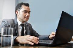 Homme d'affaires asiatique dans le costume gris employant et regardant à l'ordinateur portable salut Image libre de droits