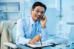 Homme d'affaires asiatique de sourire appelle quelqu'un Photo libre de droits