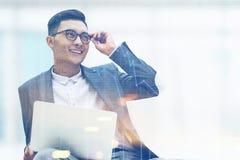Homme d'affaires asiatique de sourire avec l'ordinateur portable et les verres Photos libres de droits