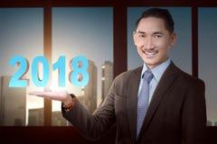 Homme d'affaires asiatique de sourire avec 2018 nombres dans sa main Image stock