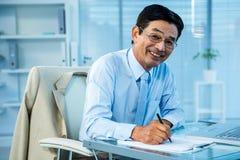 Homme d'affaires asiatique de sourire rédigeant un rapport Photos libres de droits