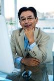 Homme d'affaires asiatique de sourire travaillant sur l'ordinateur Photographie stock libre de droits