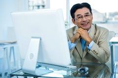 Homme d'affaires asiatique de sourire travaillant sur l'ordinateur Photos stock