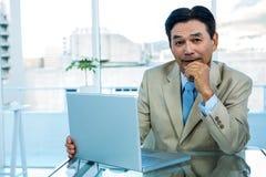 Homme d'affaires asiatique de sourire travaillant sur l'ordinateur portable Photos stock