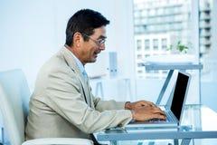 Homme d'affaires asiatique de sourire travaillant sur l'ordinateur portable Image libre de droits