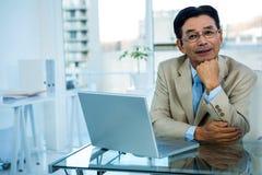 Homme d'affaires asiatique de sourire travaillant sur l'ordinateur portable Photographie stock libre de droits