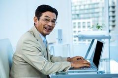 Homme d'affaires asiatique de sourire travaillant sur l'ordinateur portable Photographie stock