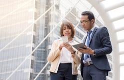 Homme d'affaires asiatique et femme d'affaires discutant des idées avec utiliser le comprimé numérique et le téléphone portable photos libres de droits