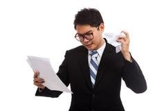 Homme d'affaires asiatique fâché avec le mauvais papier de rapport Photographie stock libre de droits