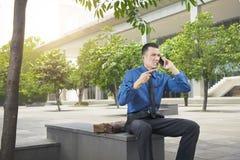 Homme d'affaires asiatique fâché tout en parlant sur son téléphone portable Photos stock