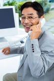 Homme d'affaires asiatique faisant un appel téléphonique Photos libres de droits