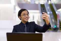Homme d'affaires asiatique heureux à l'aide de l'ordinateur portable et prenant le selfie à l'intérieur de l'immeuble de bureaux images libres de droits