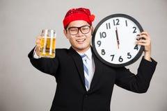 Homme d'affaires asiatique heureux avec de la bière et l'horloge à minuit Image stock