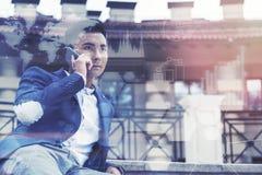 Homme d'affaires asiatique inspiré au téléphone en dehors des graphiques Photographie stock libre de droits