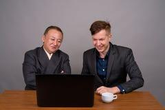 Homme d'affaires asiatique mûr et jeune agai scandinave d'homme d'affaires photos stock