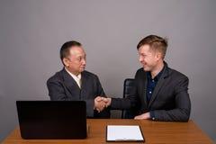 Homme d'affaires asiatique mûr et jeune agai scandinave d'homme d'affaires image stock