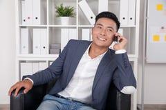 Homme d'affaires asiatique parlant à son épouse au téléphone Photo libre de droits