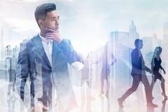 Homme d'affaires asiatique réfléchi dans la ville photo stock