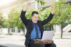Homme d'affaires asiatique réussi avec son ordinateur portable Photo stock