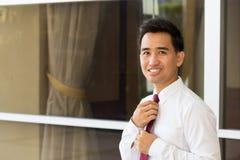 Homme d'affaires asiatique redressant le sien lien Images stock