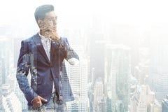 Homme d'affaires asiatique songeur dans une ville grise Photos stock