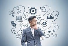 Homme d'affaires asiatique songeur et plan d'action image libre de droits