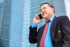 Homme d'affaires asiatique supérieur dans le costume utilisant le téléphone intelligent Images stock