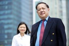 Homme d'affaires asiatique supérieur et jeune portrait de sourire exécutif asiatique femelle Image libre de droits
