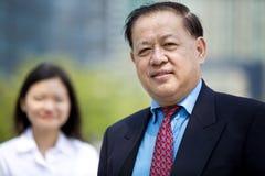 Homme d'affaires asiatique supérieur et jeune portrait de sourire exécutif asiatique femelle Photo stock