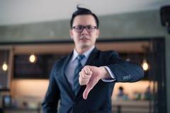 Homme d'affaires asiatique tenant et montrant le pouce vers le bas Photographie stock