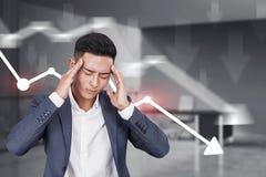 Homme d'affaires asiatique triste, graphique en baisse photos stock