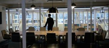 Homme d'affaires Aspirational se tenant dans la salle de conférence vide regardant la fenêtre images libres de droits