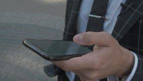 Homme d'affaires attachant du ruban adhésif au message textuel sur son smartphone Utilisant la technologie moderne pour la tâche  banque de vidéos