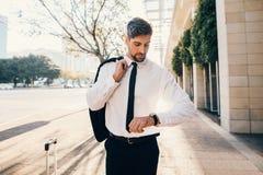 Homme d'affaires attendant en dehors de l'aéroport et vérifiant le temps Photo libre de droits