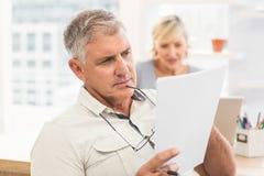 Homme d'affaires attentif lisant un document image stock