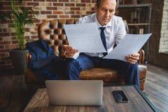 Homme d'affaires attentif regardant par des documents Image stock