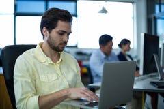 Homme d'affaires attentif utilisant l'ordinateur portable photographie stock