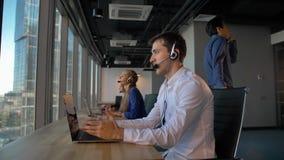 Homme d'affaires attirant au centre d'appels de bureau parlant avec le client et puis le sourire à la caméra banque de vidéos