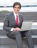Homme d'affaires attirant avec les cheveux noirs et l'ordinateur Photos stock