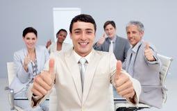 Homme d'affaires attirant et son équipe avec des pouces vers le haut Image libre de droits