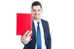 Homme d'affaires attirant gai donnant un livre et un sourire Photographie stock libre de droits