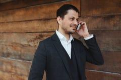 Homme d'affaires attirant parlant sur le téléphone portable et le sourire Photographie stock