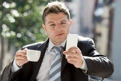 Homme d'affaires attirant s'asseyant dehors dans la pause-café utilisant le téléphone portable vérifiant des actualités de Ne de  photo libre de droits