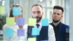 Homme d'affaires attirant travaillant avec les notes collantes colorées multi au bureau prévoyant et faisant un brainstorm banque de vidéos