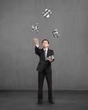 Homme d'affaires attrapant et jetant des symboles d'argent du ruban 3D Photographie stock libre de droits