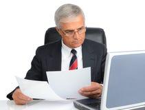 Homme d'affaires au bureau avec l'ordinateur et les papiers Image stock