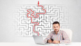 Homme d'affaires au bureau avec le labyrinthe et la flèche Photos libres de droits