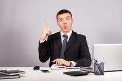 Homme d'affaires au bureau tenant le doigt : idée ou avertissement sur le fond gris Images libres de droits