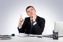 Homme d'affaires au bureau tenant le doigt : idée ou avertissement sur le fond gris Photographie stock libre de droits