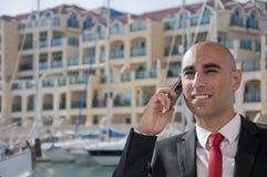 Homme d'affaires au téléphone à la marina Images stock
